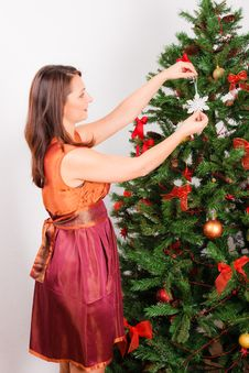 Young  Woman Decorating  A Fir-tree