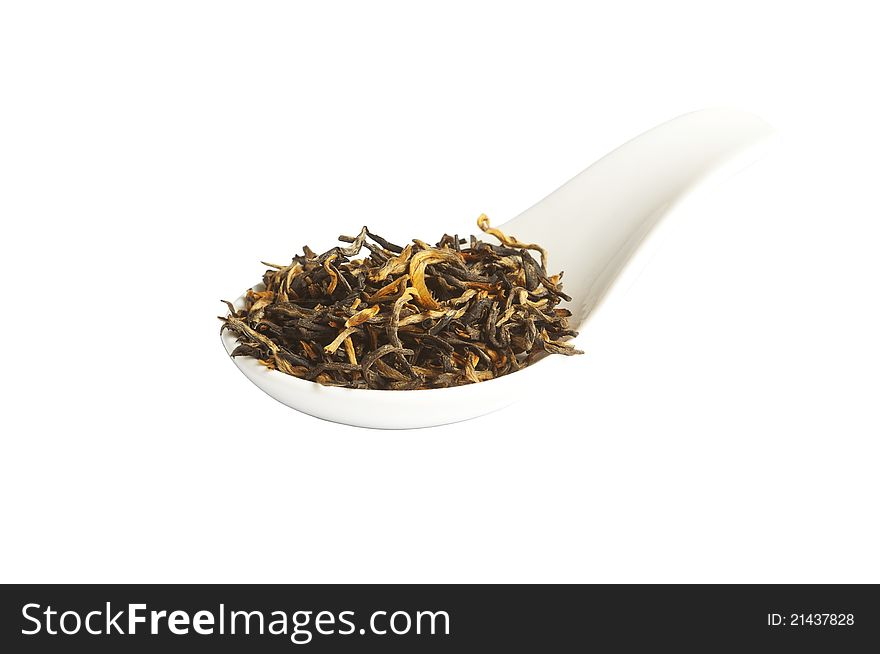 Black loose dried tea leaves in spoon, isolated