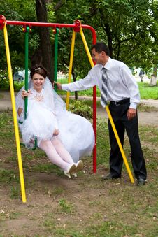 Free Bride Sitting On Swings And Groom Standing Near Royalty Free Stock Photo - 21461345