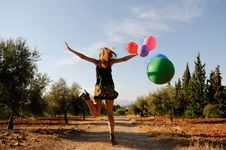 Girl With Balloons In The Field Stock Image