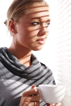 Free Beautiful Woman With Cup Of Coffee Beside A Window Stock Photography - 21522032