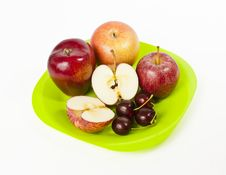 Red Big Apple And Cherry On Green Plate Isolated O Royalty Free Stock Image