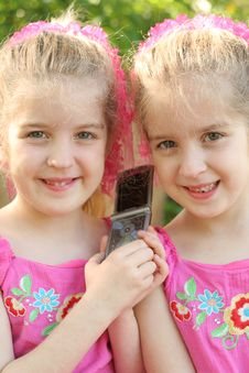 Twin Girls Sharing A Cell Phon Royalty Free Stock Image
