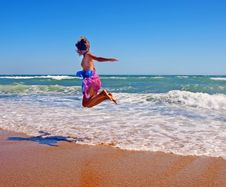 Free Girl In Pareo Jumping On The Coastline Stock Photos - 21606383