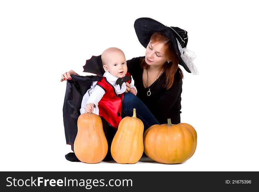 Halloween baby boy with mother witch near pumpking