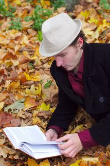 Free Man With Hat Reading Book In Autumn Leaves Royalty Free Stock Image - 21730786