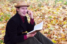 Free Man With Hat, Phone, Book In Autumn Leaves Stock Image - 21730791