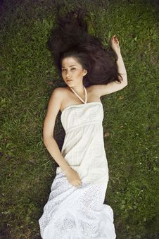 Free A Girl With Long Dark Hair Wearing Lying On Grass Royalty Free Stock Photos - 21897578