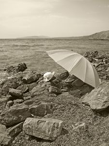 Free Summer Hat And Umbrella On A Stony Beach Stock Photography - 21909972