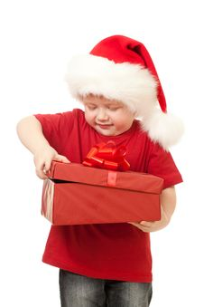 Adorable Boy In Santa Hat Opening Christmas Gift Royalty Free Stock Photos