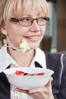 Free Adult Blonde Woman In Glasses Eats Salad Royalty Free Stock Image - 22064106