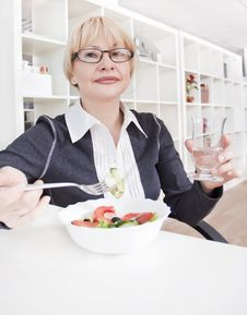 Adult Blonde Woman In Glasses Eats Salad Royalty Free Stock Image