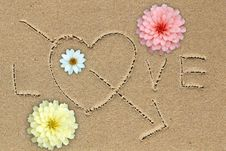 Love Word With Love Sign And Flowers On Sand Stock Photos