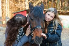 Two Girls Playing With Horse Stock Photo