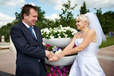 Happy Groom And Happy Bride Near Flowers Bed