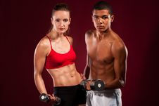 Strong Young Couple Working Out With Dumbbells Stock Photography