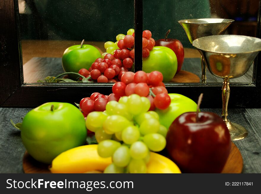 Fruit tray, silver wine glass with reflection through mirrored window