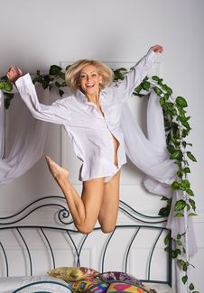 Young Woman Jumping On The Bed Royalty Free Stock Photos