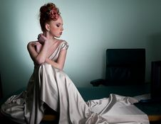 Redhead Girl In Long Dress Sitting On Office Desk Stock Photography