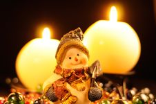 Snowman Figurine And Burning Candles Royalty Free Stock Photos