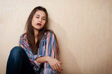 Depressed Woman Sitting By The Wall Stock Photo