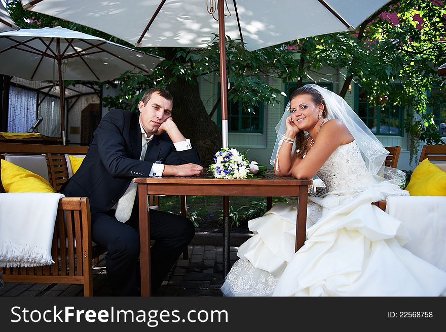 Bridal couple sitting on benches in cafe