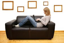 Young Woman Lying On A Sofa And Using A Laptop Stock Image