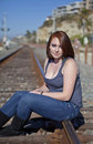 Free Cute Teen Girl Sitting On Rail Road Tracks Royalty Free Stock Image - 22725126