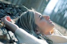 Beautiful Blonde Girl Lying On Leaves Royalty Free Stock Photo