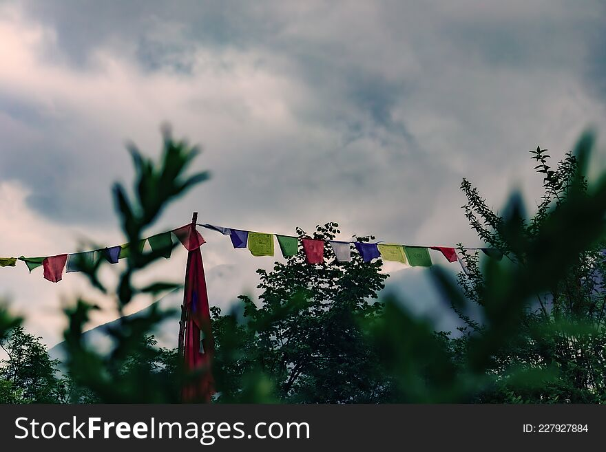 Colored tibetan flags. Vegetation on the foreground. Clouds and mountains on the background. Concept of tibetan culture, buddhism