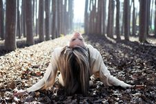 Beautiful Blonde Girl Lying On Leaves Royalty Free Stock Image