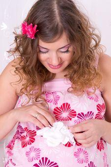 Pregnant Girl In Pink Dress Holding Baby Socks Stock Image