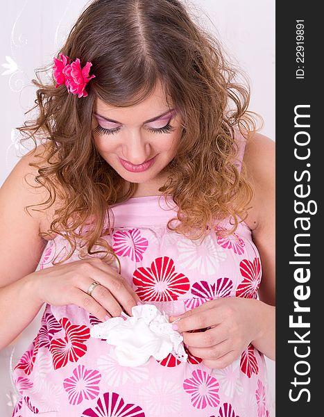 Pregnant girl in pink dress holding baby socks