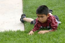 Free Boy Resting On The Grass Royalty Free Stock Photography - 230897