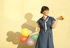Free The Girl  Of The Wall Keeps Apple And Balloons Royalty Free Stock Image - 23087566