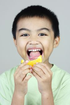 Free Boy Eating Orange Slice Stock Images - 23093894
