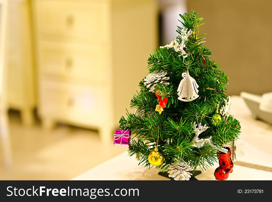 Small decorated Christmas tree on table