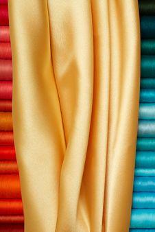 Colored Bobbins And Golden Silk Stock Photos