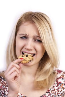 Free Young Woman Eating Cookie With Grimace Royalty Free Stock Image - 23259626