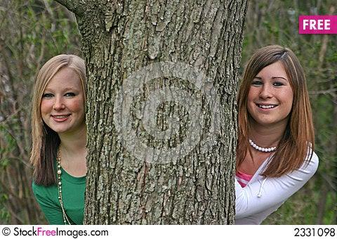 Free Girls Peeking Around A Tree Royalty Free Stock Photos - 2331098