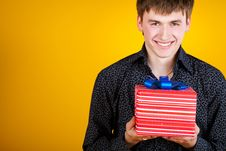 Free Present Gift Holding Man Looking Camera Royalty Free Stock Photography - 23331207