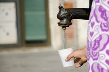 Filling A Cup With Water In The Street Stock Photos