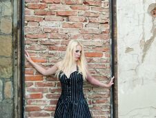 Free Blond Gothic Girl In Front Of A Brick Wall Royalty Free Stock Photos - 23404838