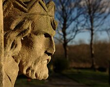 Free Stone Head Overlooking Churchyard Stock Photography - 23447332