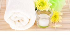Towel, Candle And Two Yellow Flowers Royalty Free Stock Photos