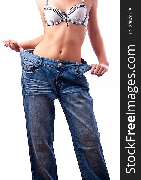 Athletic muscular female body in old trousers