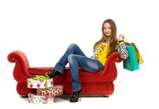 Beautiful Girl  With Parcels Lying On The Red Sofa Stock Photo
