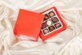 Free Box Of Chocolates On White Satin Background Stock Images - 23622494