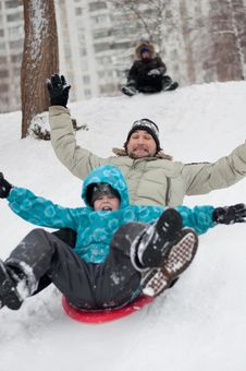 Dad And Son Riding From Frozen Hill Stock Photos