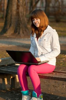 Pretty Teenage Girl Typing On Notebook In The Park Royalty Free Stock Photography